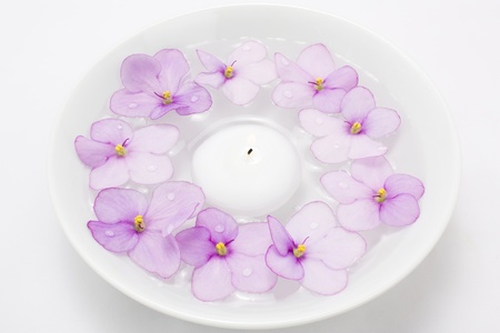 Floating candle in water and lilac flower Stock Photo
