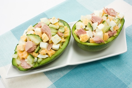 Avocado stuffed with tuna, cucumbers, eggs and cheese