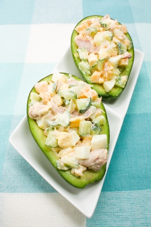 Avocado stuffed with tuna, cucumbers, eggs, cheese and mayonnaise Stock Photo