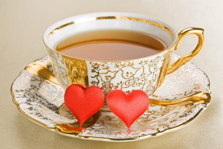 Gold antique cup tea with two red hearts
