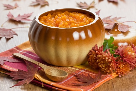 Pumpkin soup in ceramic pot, wooden spoon, flower and autumn leaf shallow DOF  Stock Photo