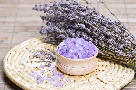 Aromatic bath salt and dry lavender flowers on bamboo mat shallow DOF
