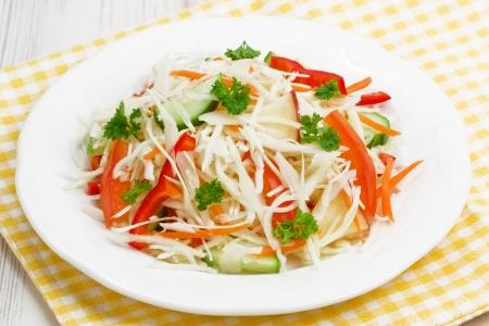 Cabbage spring salad with tomato, cucumber, red pepper,  apple and carrot Stock Photo