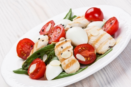 Spinach, grilled chicken, cherry tomatoes, and quail eggs salad with almond chips and balsamic vinegar