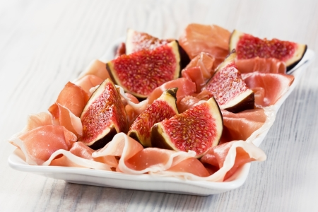 Prosciutto cured ham with ripe figs on white plate Stock Photo