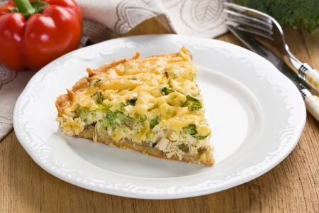 Quiche pie with broccoli, chicken and ham on white plate