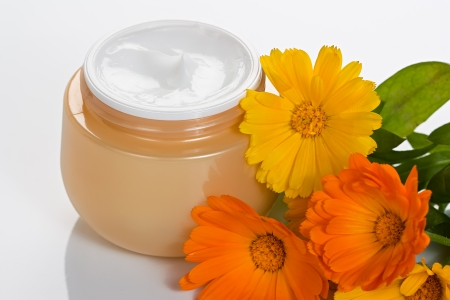 Cosmetic moisturizing facial and body cream in jar with flower Stock Photo