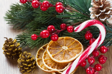 christmas tree decorations with dried orange slices holly berries and candy on wooden background stock