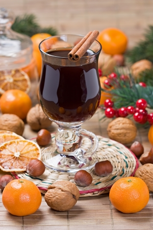 Mulled wine winter hot drink with cinnamon, dried orange slices, tangerine and walnut