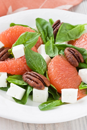 Spinach grapefruit goat cheese salad with pecan nut on white plate Stock Photo