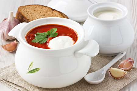 Beetroot soup red borscht with sour cream in white bowl