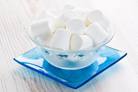 Marshmallow sweets candies in glass bowl on wooden background