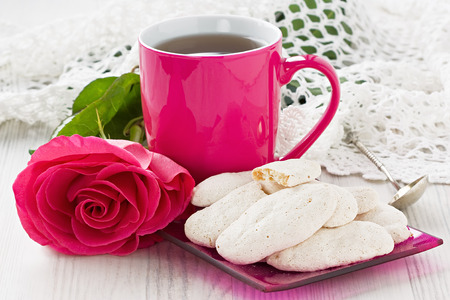 Cup tea with almond cookies and rose on wooden background Stock Photo