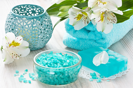 Aroma SPA set with sea salt, natural soap, soft towel and flower on wooden background
