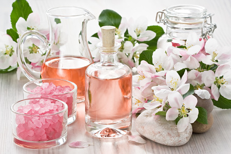 Aroma oil, sea salt, and apple blossom flower on wooden background