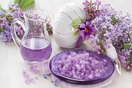 Aroma oil, sea salt, herbal massage bag and lilac flower on wooden background