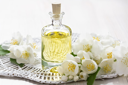 perfume oil: Essential oil with jasmine flower on wooden background