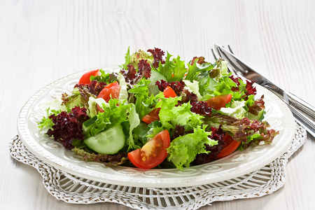 Fresh salad with green, red lettuce, tomato and cucumber