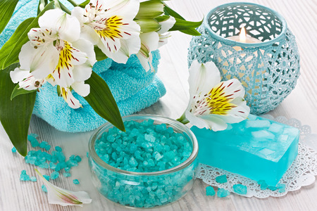 blue candles: Sea salt, aroma candle, natural soap, soft towel and flower on wooden background