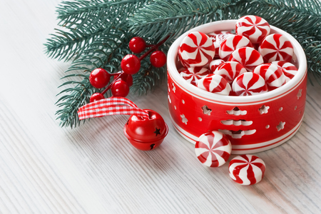 jingling: Peppermint sweet candy and Christmas decoration with jingle bell and pine branch