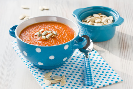 Pumpkin soup with seeds in blue bowl on wooden background Stock Photo