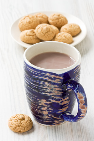Hot cocoa drink in blue rustic mug and amaretti biscuits cookies Stock Photo