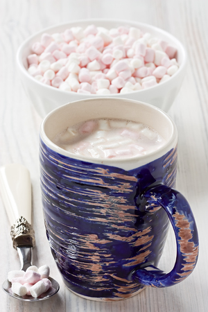 Hot cocoa beverage in blue rustic mug with marshmallow sweets Stock Photo