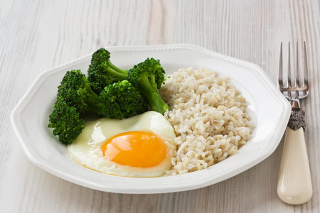 Healthy breakfast with egg, brown rice and broccoli