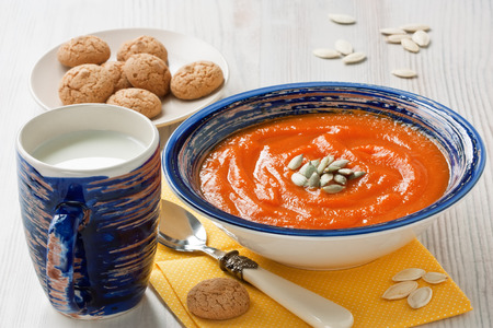 Pumpkin soup with seeds, cup milk and cookies on wooden background