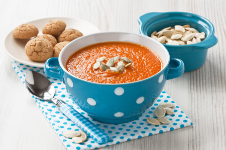 Pumpkin soup with seeds and cookies in blue bowl on wooden background
