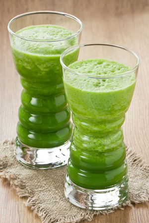 Fresh spinach and green apple smoothie in two glass on wooden background
