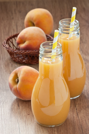 Fresh peach juice delicious summer drink and ripe peach fruit on wooden background