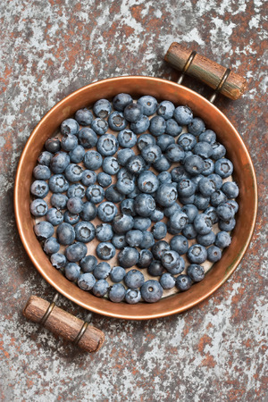 Blueberries on rustic copper tray and rusty metal background