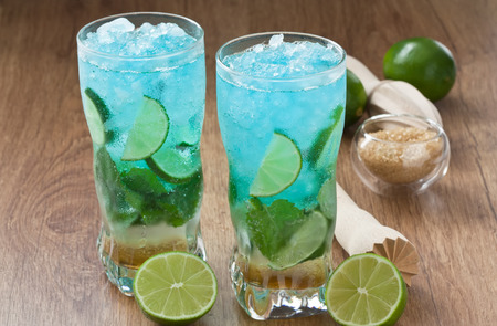 Blue mojito cocktail refreshing summer drink with lime, mint and ice on rustic wooden table