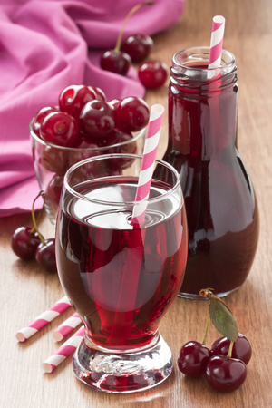 Fresh cherry juice and cherry fruit delicious summer drink on wooden background