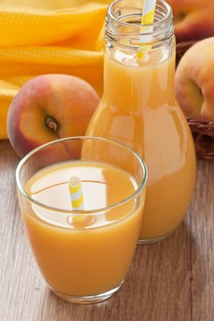 Glass fresh peach juice and ripe peach on wooden background