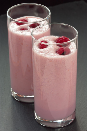 Delicious fresh raspberry milkshake or yogurt on dark background