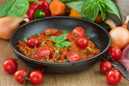 Tomato sauce bolognese for spaghetti with cherry tomato, basil and vegetable on rustic wooden background