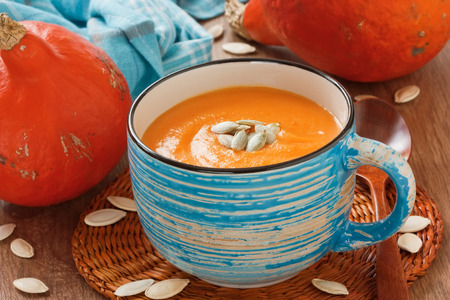 Pumpkin soup with seeds in cup on rustic wooden background Stock Photo