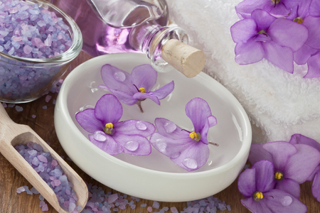 Floating violet flower in water, aromatic essential oil, sea salt and soft towel on wooden background