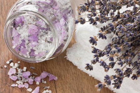 Aromatic sea salt, lavender dried flower and soft towel on wooden background   Stock Photo
