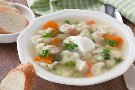 Vegetable soup with chicken, cauliflower, carrot, potato, parsley, cream and slice white bread in plate on wooden background