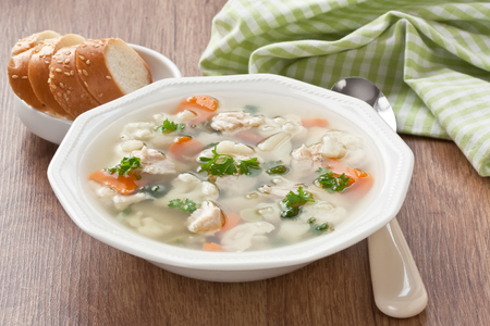 Vegetable soup with chicken, cauliflower, carrot, potato, green peas, parsley and slice white bread in plate on wooden background