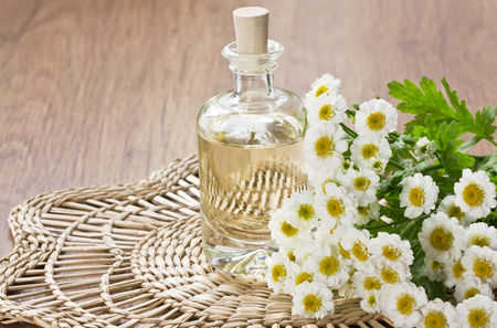 Essential aroma oil with chamomile flower for aromatherapy, spa, massage on bamboo mat
