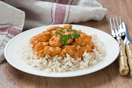 Chicken curry with brown rice in white plate on wooden background