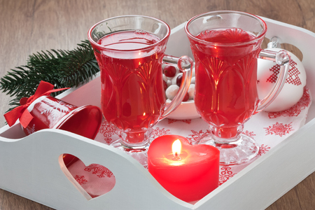 Cranberry hot winter drink in glass, berry sugar sweets on white wooden tray with candle, decorated ball and bell  Stock Photo