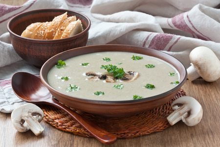 Creamy mushroom soup with fried mushrooms and parsley in bowl on wooden background