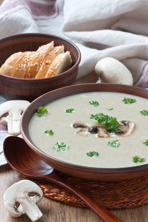 Creamy mushroom soup with fried mushrooms, parsley in bowl and white bread on wooden background