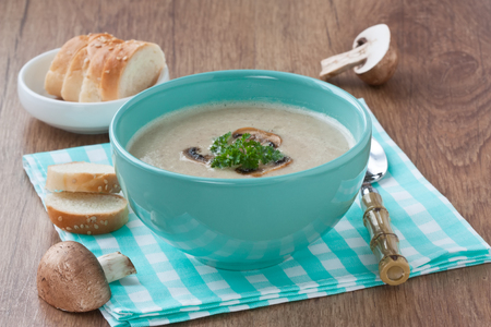 Creamy mushroom soup in blue bowl with fried mushrooms, parsley and white bread on wooden background