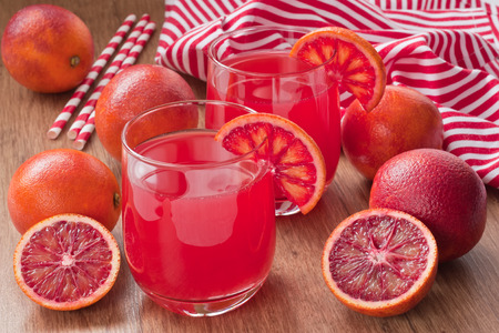 Glass fresh juice drink and red bloody Sicilian oranges on wooden background